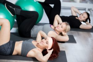 Fitness practice, group of three happy smiling beautiful fit young females working out in sports club, doing exercise for abdominal muscles on green Swiss balls in class